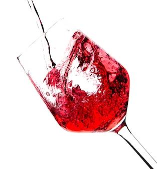 Vinho tinto está sendo derramado em uma taça de vidro sobre um fundo branco. bebidas alcoólicas. foto de alta qualidade