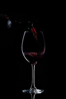 Vinho tinto está sendo derramado em vidro com haste longa no escuro