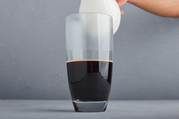 Vinho tinto ou suco em um copo grande na superfície cinza.