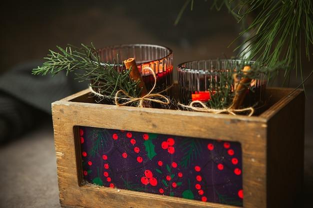 Vinho tinto quente de natal com especiarias aromáticas e frutas cítricas em caixa de madeira, close-up. bebida quente tradicional na época do natal