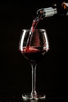 Vinho tinto sendo derramado em um copo de vinho