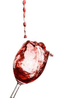 Vinho tinto sendo servido em um copo em uma superfície branca