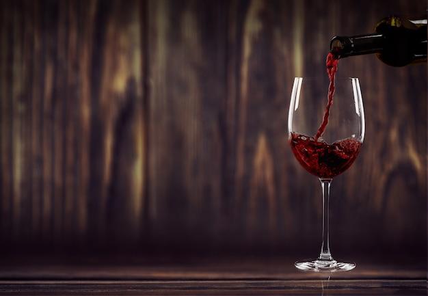 Vinho tinto servindo em um copo com fundo de madeira