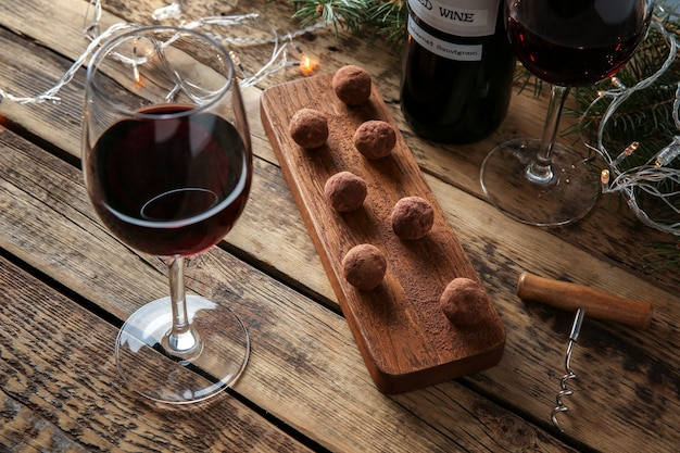 Vinho tinto, sobremesa de chocolate e enfeites de natal na mesa de madeira