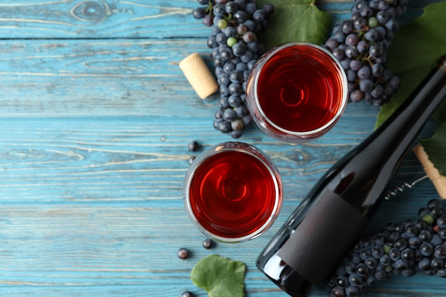 Vinho tinto, uva, cortiça e saca-rolhas na mesa de madeira