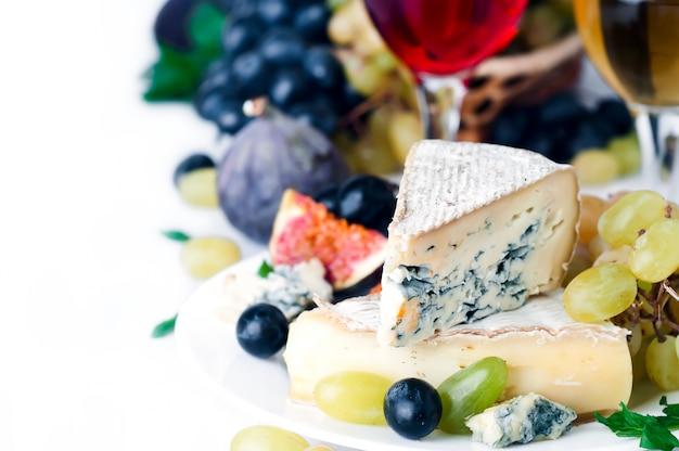 Vinho, uva e queijo sobre branco