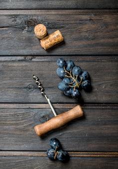 Vinho. uvas com saca-rolhas e rolhas de madeira.