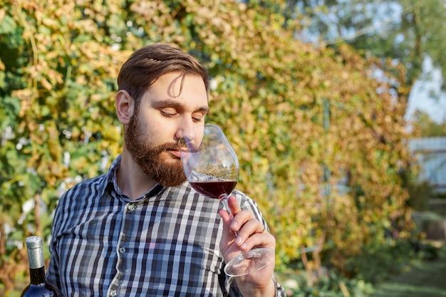 Vinicultor caucasiano bebendo um copo de vinho tinto, provando-o, verificando a qualidade de pé nos vinhedos