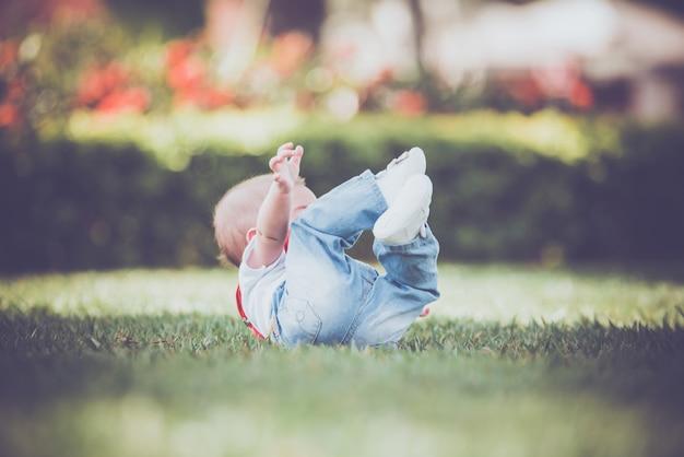 Vintage baby boy com suspensor vermelho no exterior - caindo na grama