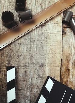 Vintage carretel câmera fita e claquete na madeira