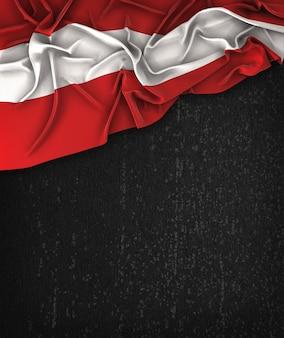 Vintage da bandeira de áustria em um quadro preto do grunge com espaço para o texto