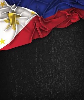 Vintage da bandeira de filipinas em um quadro preto do grunge com espaço para o texto