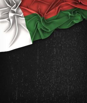 Vintage da bandeira de madagascar em um quadro preto do grunge com espaço para o texto