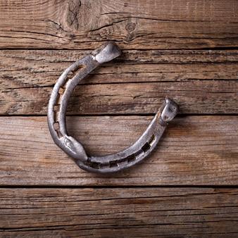 Vintage de metal ferradura resistiu ao fundo de madeira.