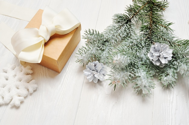 Vintage de presente de natal com ramo coberto de neve de abeto em branco