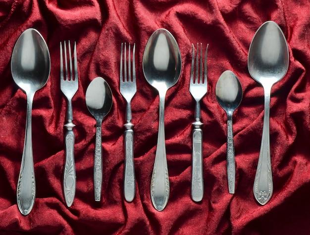 Vintage garfos e colheres numa toalha de mesa de seda vermelha. vista do topo.