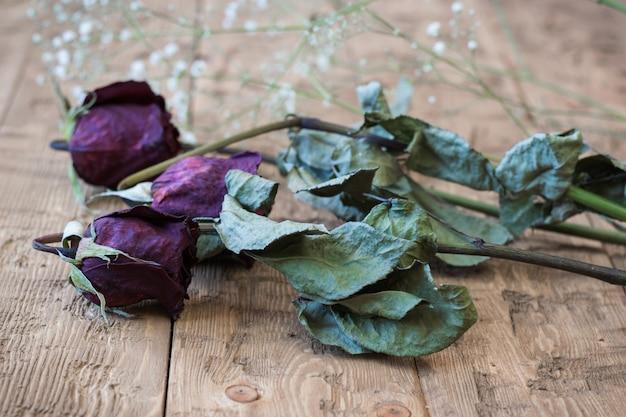 Vintage lindo rosas murchas em um fundo rústico.