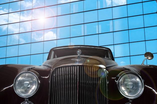 Vintage, preto, carro brilhante em um fundo de uma parede espelhada de um edifício moderno.