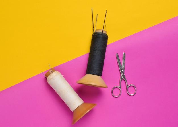 Vintage preto e branco novelos de linha com agulhas e tesouras em um fundo rosa amarelo