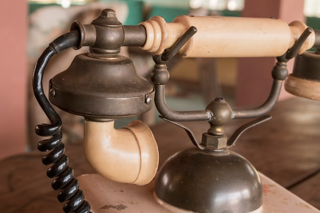 Vintage - telefone antigo bege retrô em uma mesa de madeira