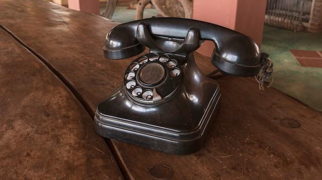Vintage - telefone antigo preto retrô em uma mesa de madeira