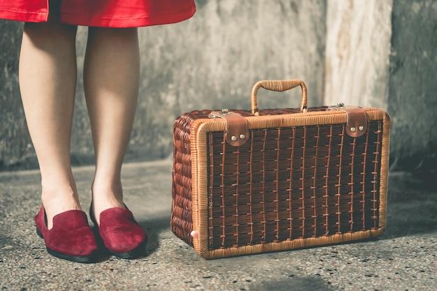 Vintage viajante chinês segurando uma mala de viagem vintage