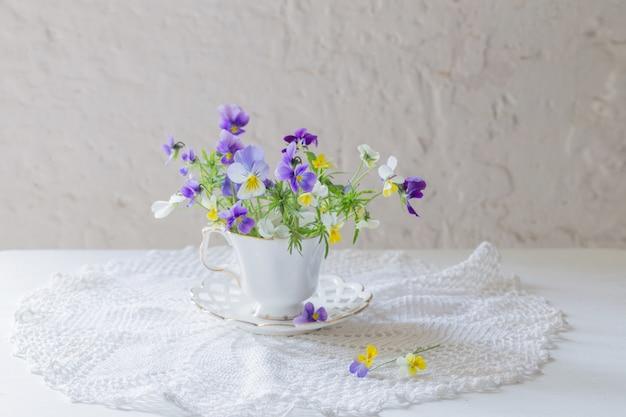 Viola flores em copo branco sobre fundo branco