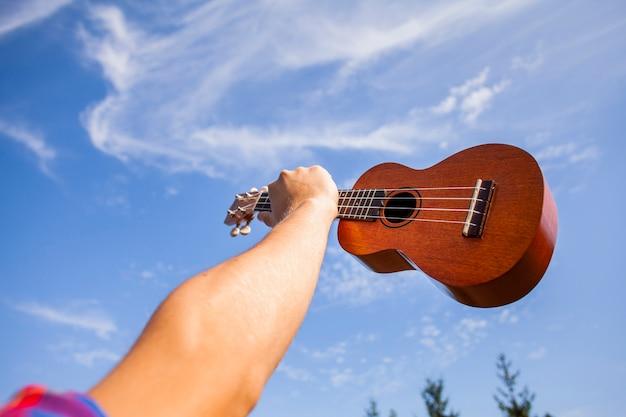 Violão ukulele sendo segurar no ar