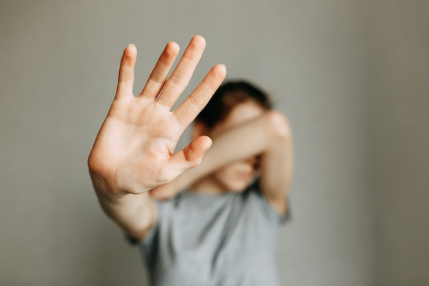 Violência doméstica contra a mulher a menina cobre o rosto com a mão e pede ajuda