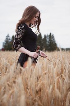 Violinista garota romântica sorridente em um campo de trigo com uma mão segurando um violino e curvar a outra orelha de graduado