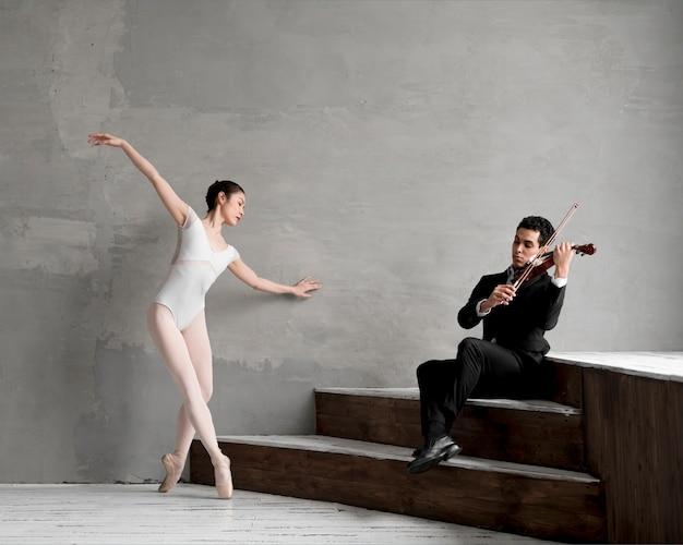 Violinista masculina tocando música enquanto dança bailarina