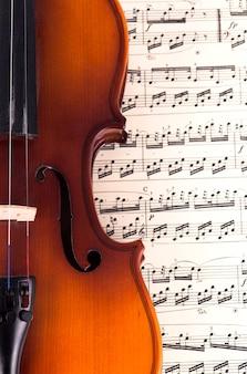 Violino antigo deitado na partitura, conceito de música