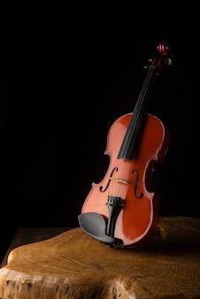 Violino antigo e bonito em uma superfície de madeira rústica e retrato de baixa chave de mesa preta, foco seletivo.