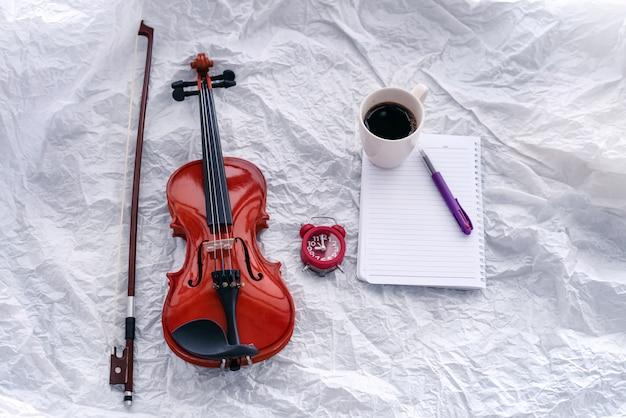 Violino e arco colocado no lado esquerdo do despertador vermelho, livro e xícara de café, na superfície do grunge