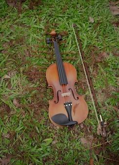Violino e arco colocados no piso térreo de grama verde, mostram detalhes do instrumento acústico