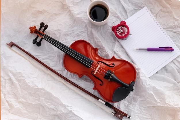 Violino e arco colocar ao lado de despertador vermelho, livro e xícara de café, na superfície do grunge
