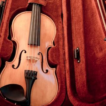 Violino e arco em estojo vermelho escuro.