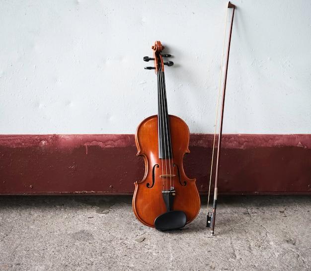 Violino e arco na superfície de cimento do piso térreo do grunge, mostram detalhes do instrumento acústico