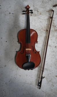 Violino e arco na superfície do grunge, mostram detalhes do instrumento acústico