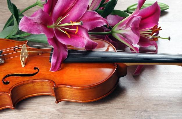 Violino e flores de lírio em uma mesa de madeira