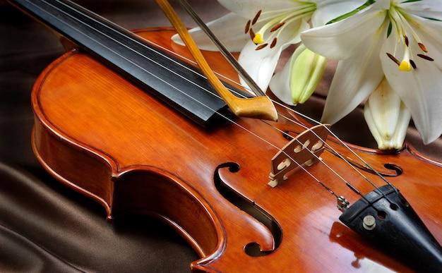 Violino e lírio em uma toalha de seda de mesa