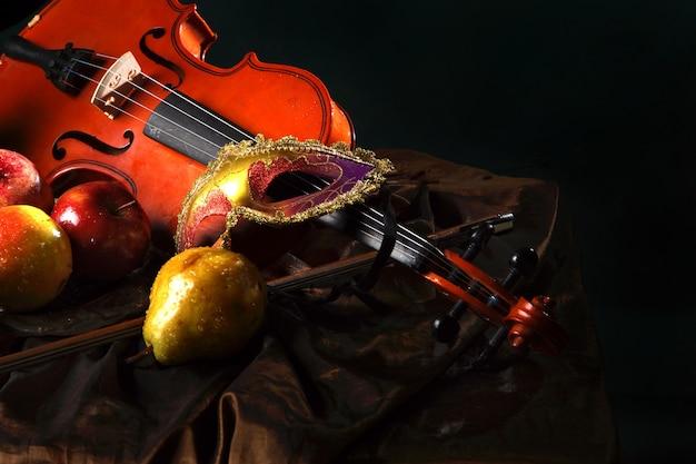 Violino e máscara teatral no tecido ao lado de frutas suculentas
