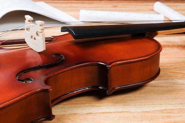 Violino e notas sobre uma mesa de madeira