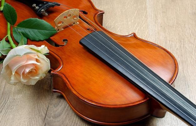 Violino e rosa branca em uma mesa de madeira.