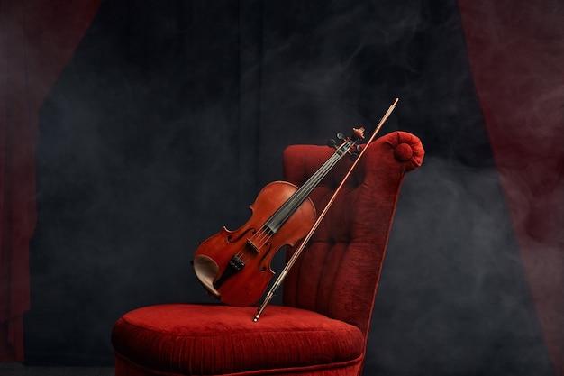 Violino em estilo retro e arco na cadeira, ninguém. instrumento musical de cordas clássico, arte musical, viola de madeira