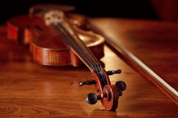 Violino em estilo retro na mesa de madeira, vista do close up, ninguém. instrumento musical de cordas clássico, arte musical, viola antiga