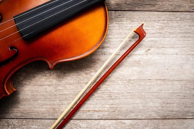 Violino marrom com vara violino na madeira