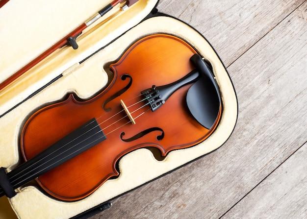 Violino marrom no caso em fundo de madeira