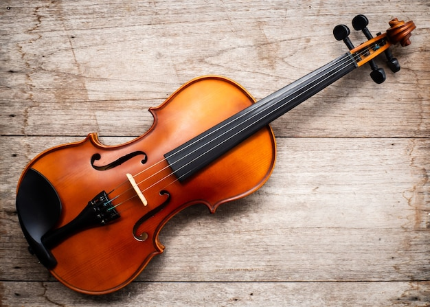 Violino marrom no fundo de madeira