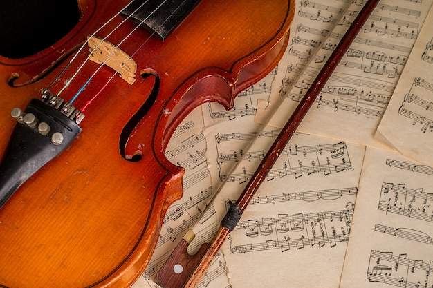 Violino velho deitado na folha de música